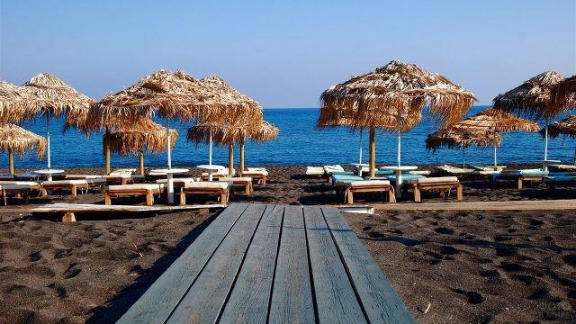 Тропические зонтики над шезлонгами на чёрном пляже Санторини