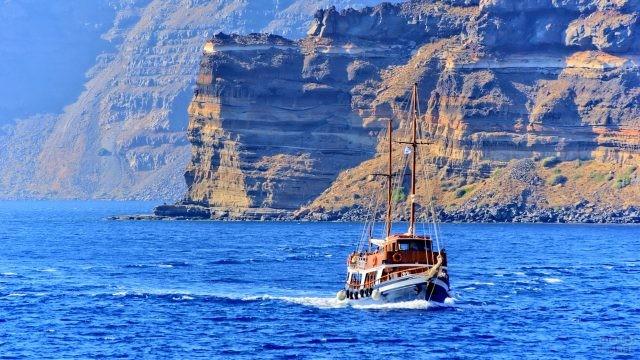 Туристический прогулочный корабль на фоне скалистого берега