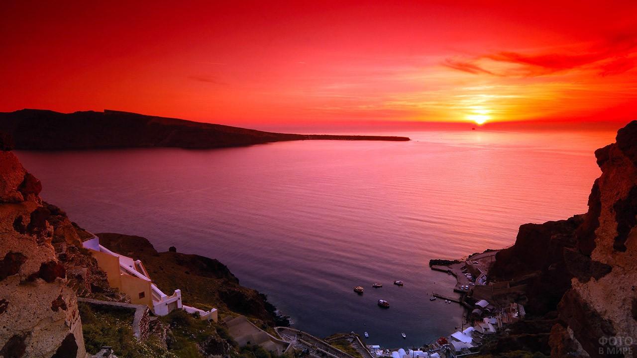 Вид на закат над морем со скалистого берега Санторини
