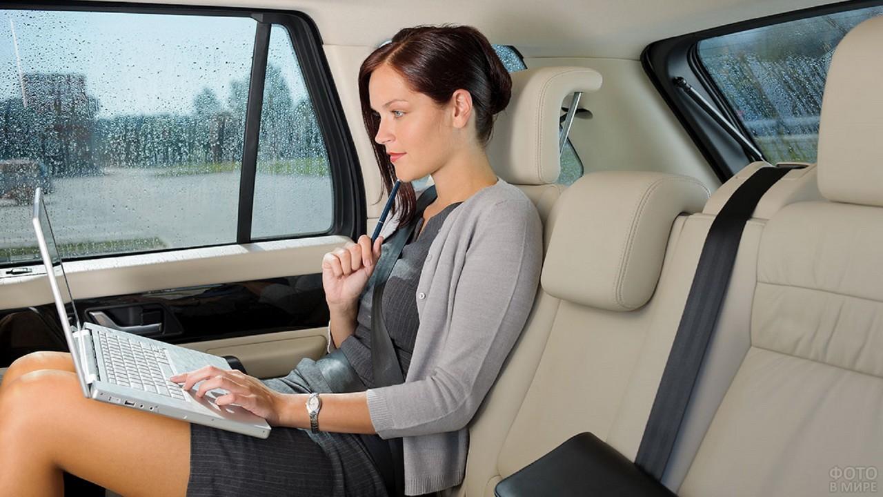 Бизнес-леди на заднем сиденье автомобиля работает в ноутбуке
