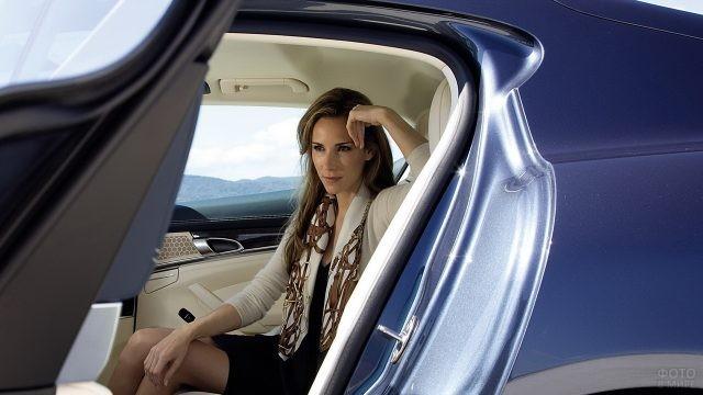 Бизнес-леди сидит на заднем сиденье синего автомобиля