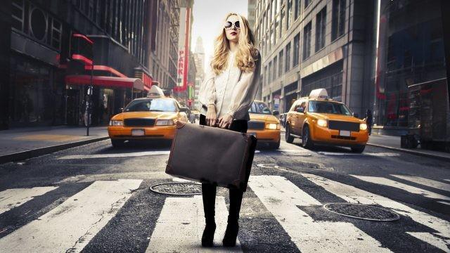 Блондинка с чемоданом на пешеходном переходе на фоне такси