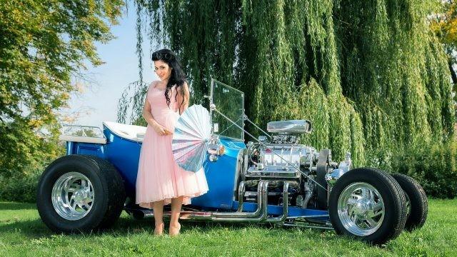 Брюнетка с зонтиком в розовом платье на фоне синего ретро-автомобиля
