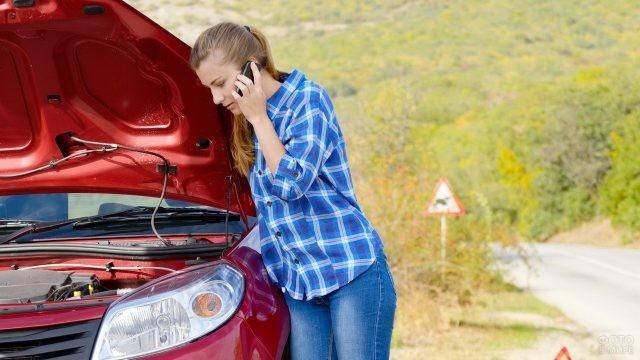 Девушка разговаривает по телефону возле красного авто с открытым капотом