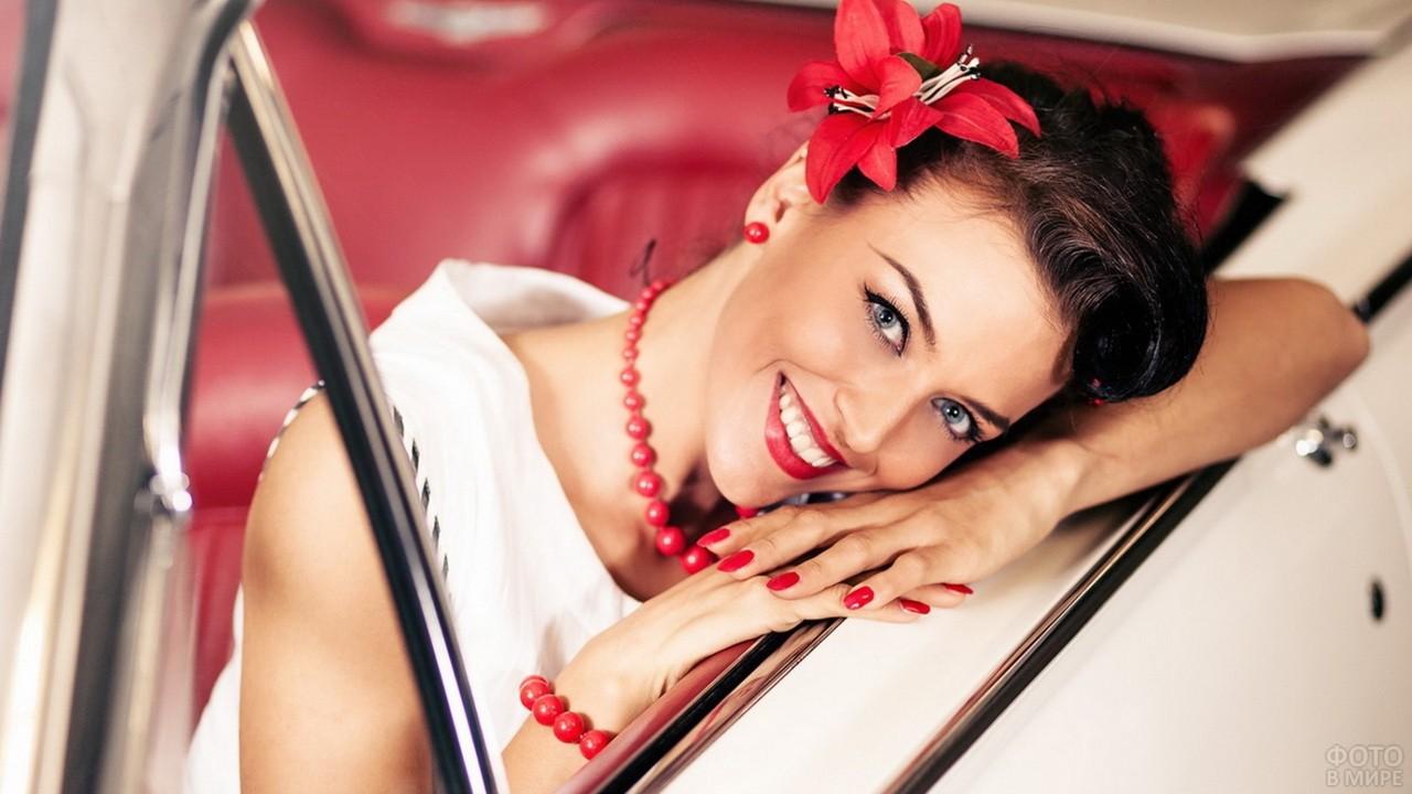 Девушка с красным цветком улыбается из окна белого кабриолета