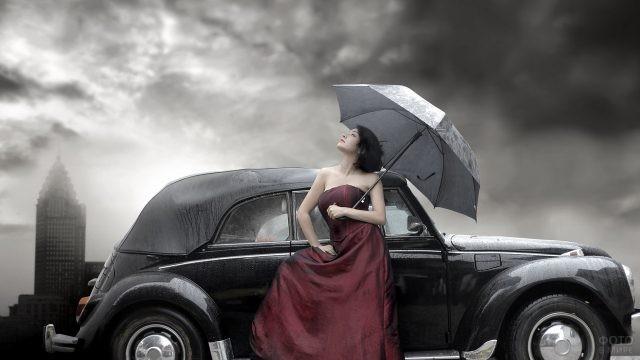 Девушка с зонтом смотрит вверх возле чёрного автомобиля