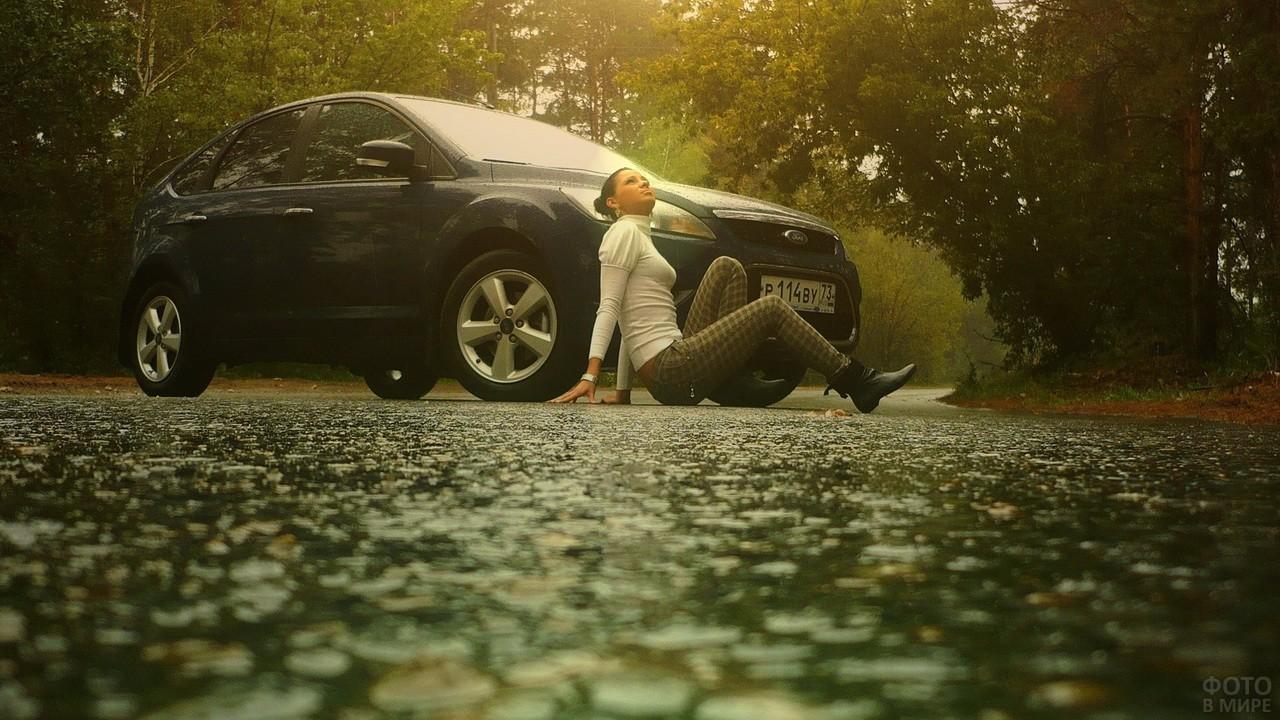 Девушка сидит на земле возле автомобиля под дождём