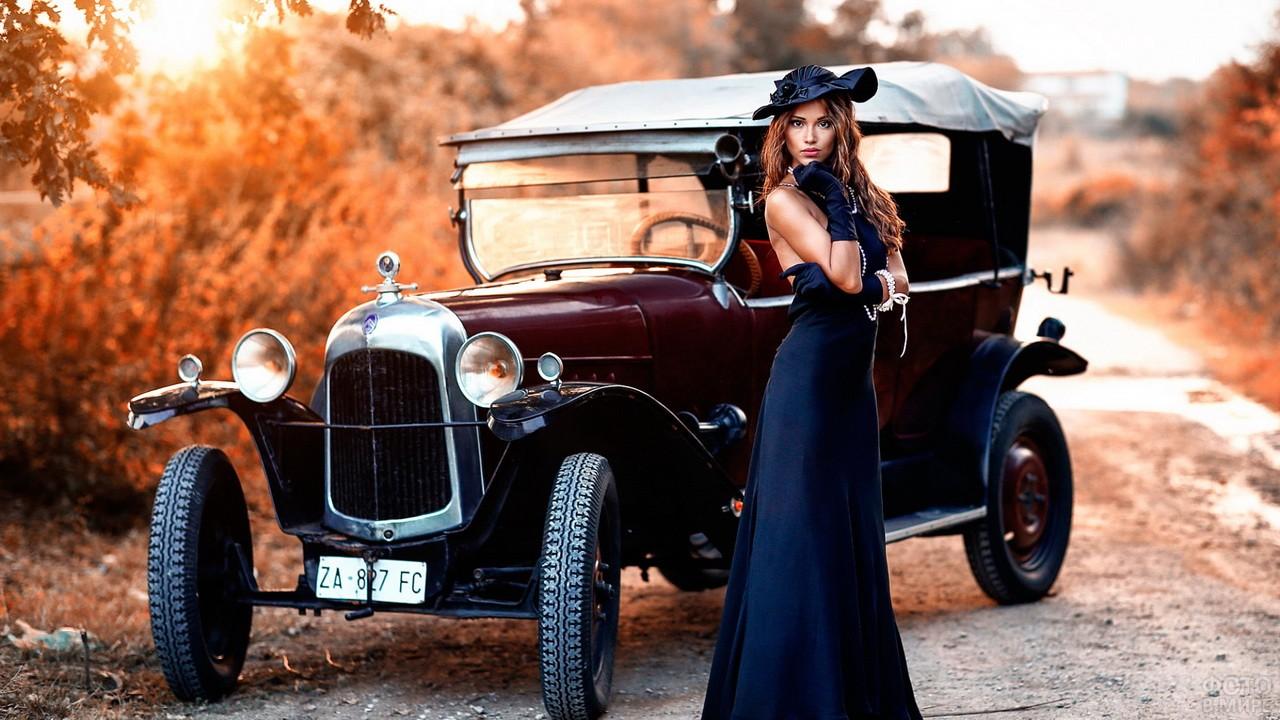 Девушка в длинном синем платье и шляпе стоит возле ретро-автомобиля