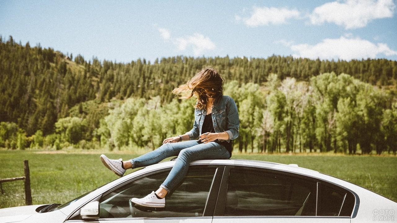 Девушка в джинсовой одежде сидит на крыше белого авто