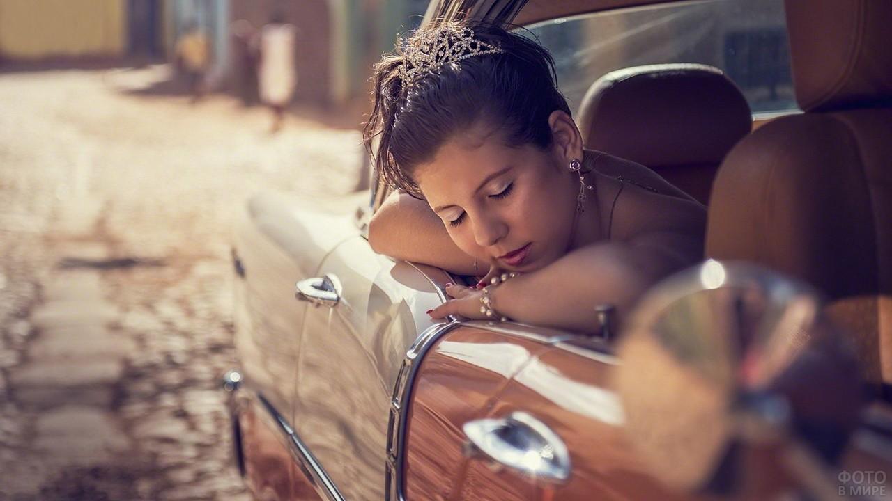 Девушка в короне спит на дверце машины