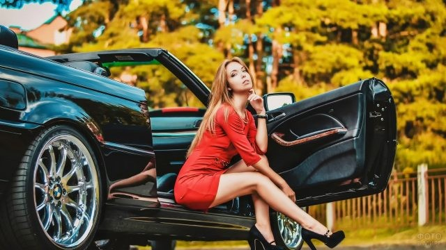 Девушка в красном платье сидит в чёрном кабриолете