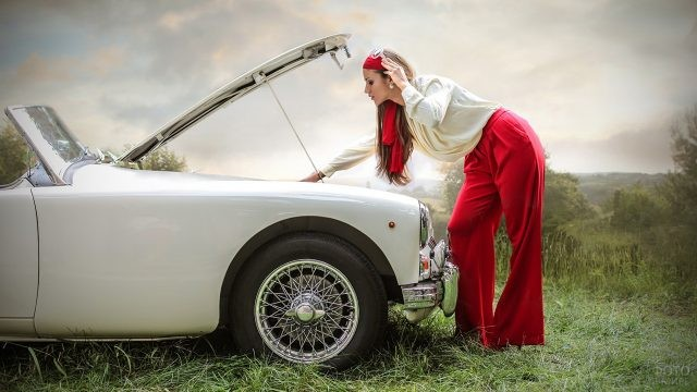 Девушка в красных брюках ремонтирует машину