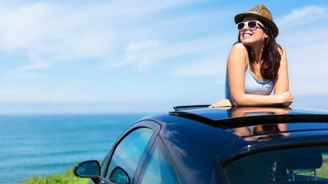 Девушка в солнцезащитных очках и шляпе смотрит на небо из люка авто