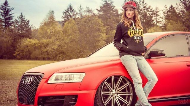 Девушка в спортивной одежде на капоте красного автомобиля