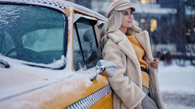 Девушка в светлой шубе и шапке-гаврош возле такси зимой