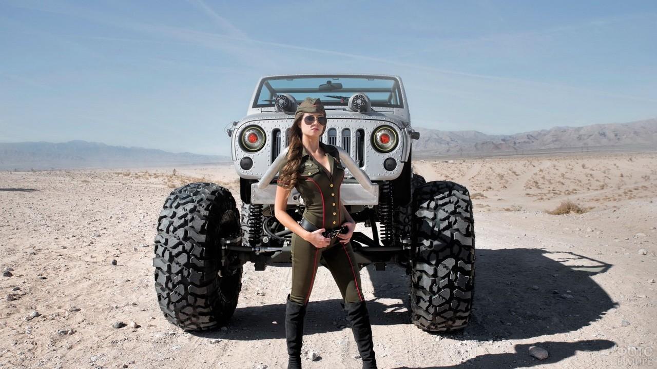 Девушка в военной форме стоит возле джипа в пустыне