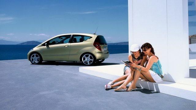 Девушки читают журнал рядом с автомобилем