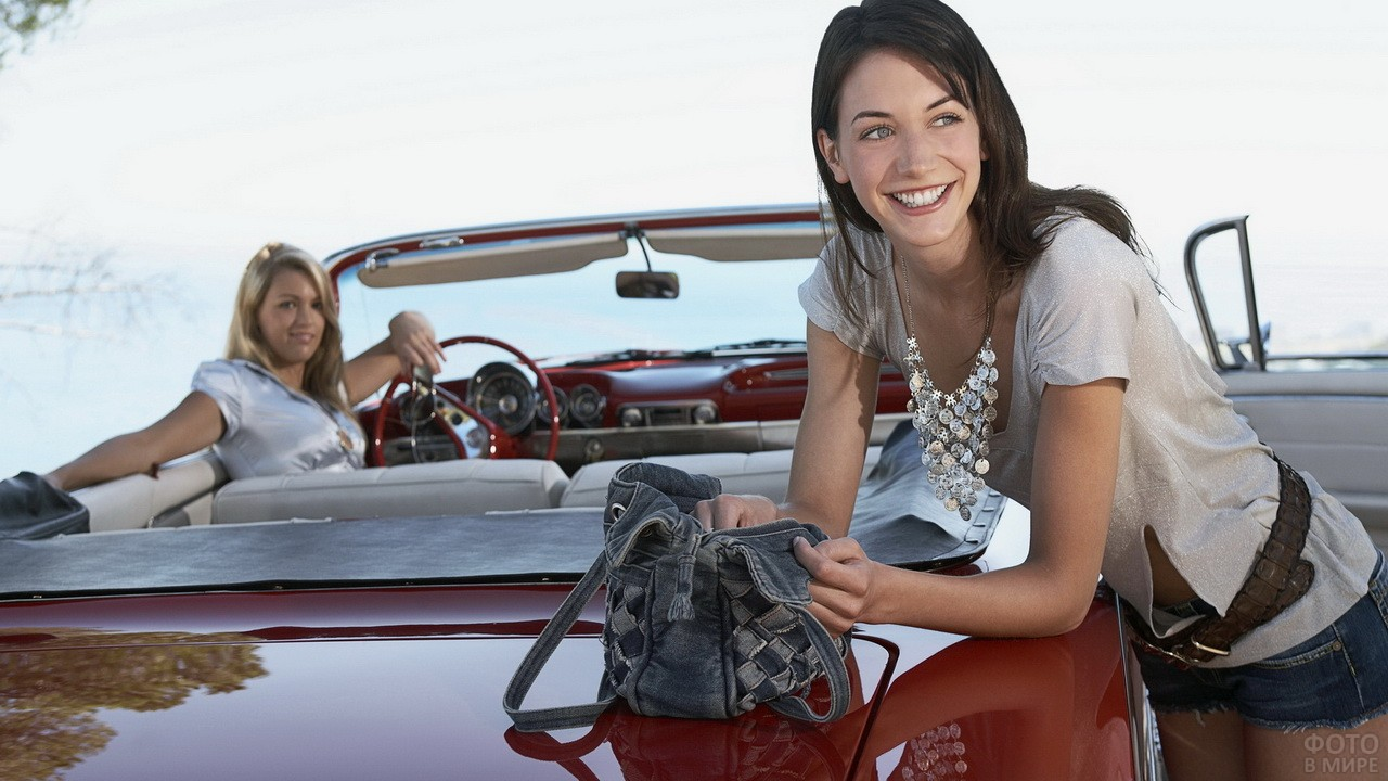 Девушки путешествуют на красном кабриолете