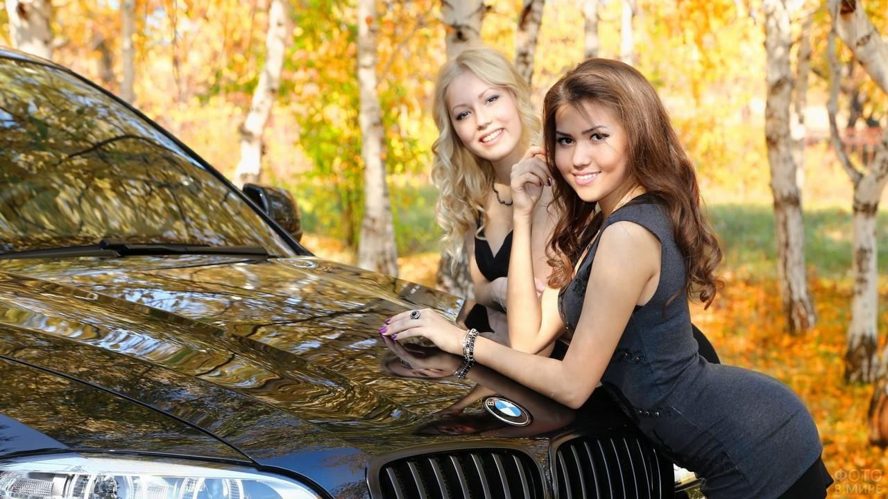 Две девушки возле чёрной машины осенью