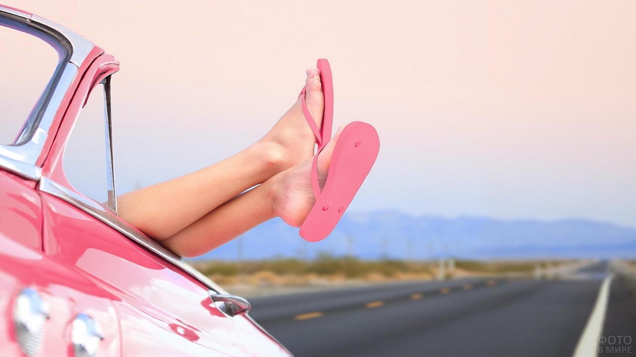 Ноги девушки в розовых сланцах высовываются из окна кабриолета