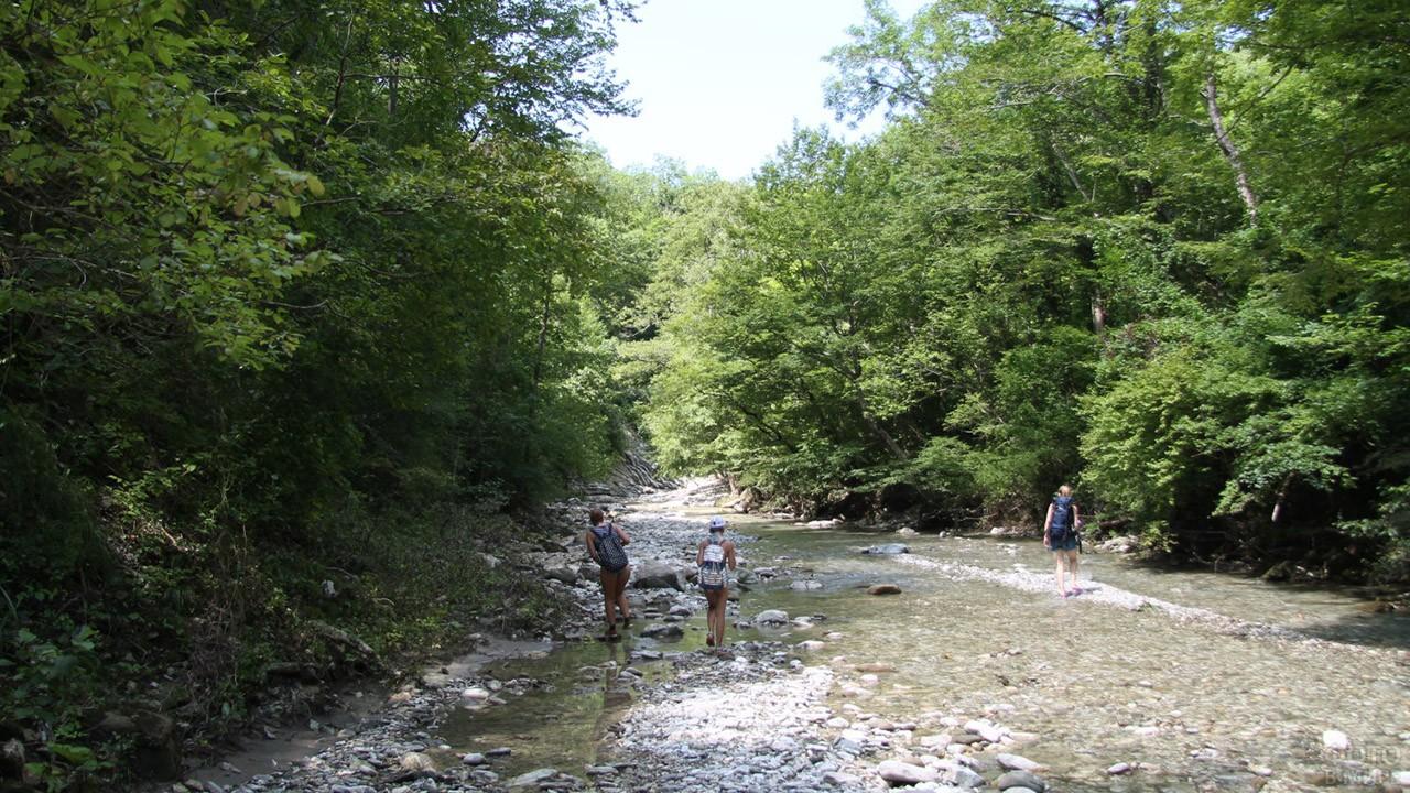 Эко-туристы идут в горы по руслу речки Кабак