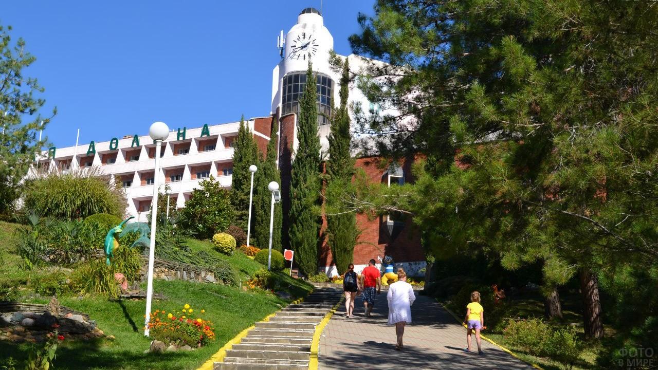 Туристы идут по аллее парка к зданию санатория