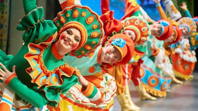 Народный коллектив в костюмах дымковской игрушки во время праздничного концерта