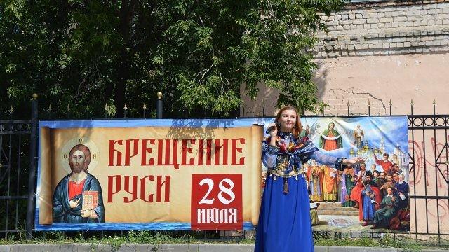 Певица в народном костюме у ворот храма с праздничным баннером