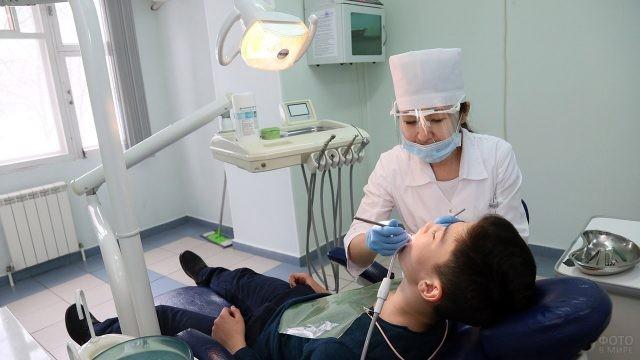 Детский стоматолог осматривает подростка