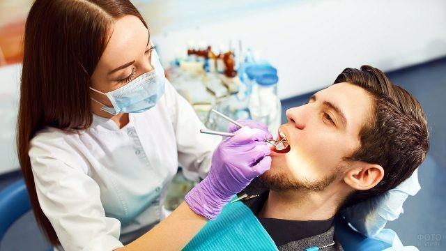 Девушка-дантист осматривает пациента