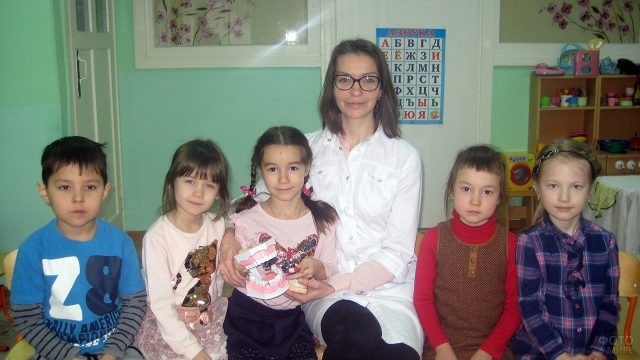 Девушка-стоматолог на уроке с малышами в детском саду