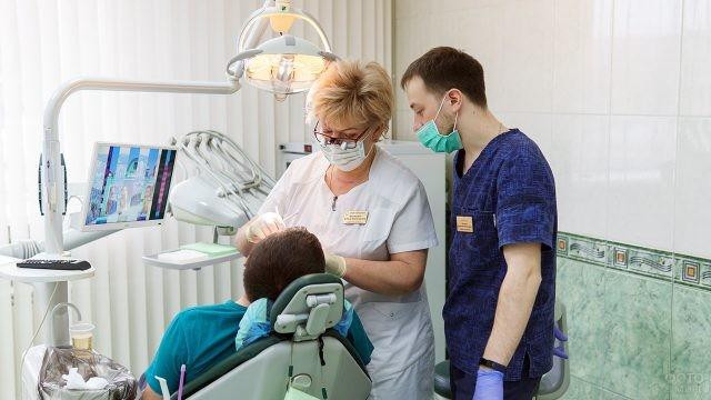 Два дантиста осматривают пациента