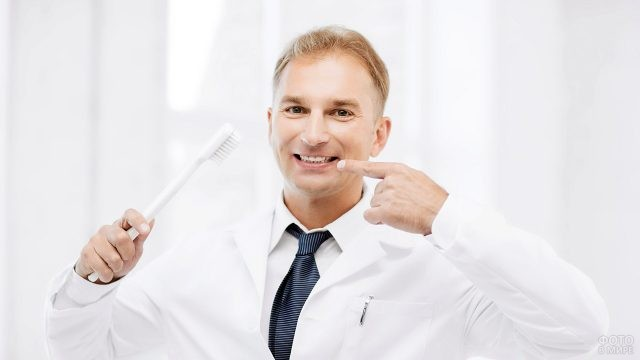 Мужчина-стоматолог держит в руках зубную щётку и улыбается