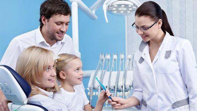 Родители с маленькой дочкой на приёме у детского стоматолога