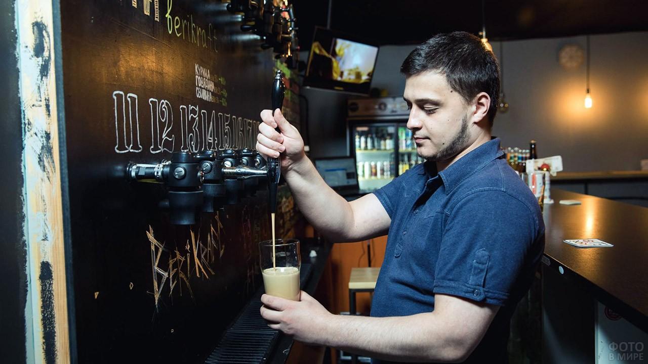 Бармен наливает один из сортов пива в пабе