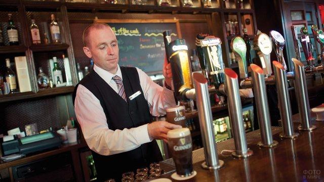 Бармен наливает знаменитое пиво Гинесс в классическом пабе