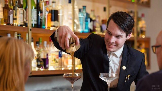 Бармен разливает коктейли гостям вечеринки