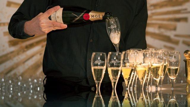 Бармен разливает шампанское по бокалам