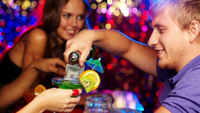Бармен в ночном клубе наливает барышням коктейль