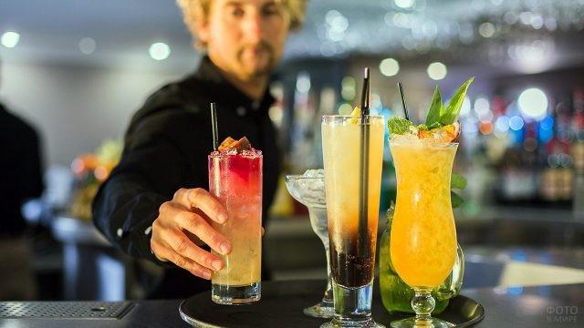 Бармен выставляет на поднос бокалы с тропическими коктейлями