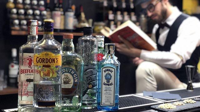 Бутылки с джином на барной стойке и бармен с книгой