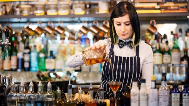Девушка-бармен наливает коктейль