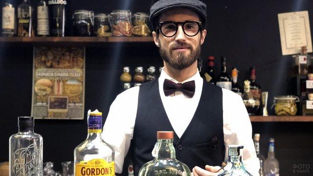 Молодой бармен в очках и кепке