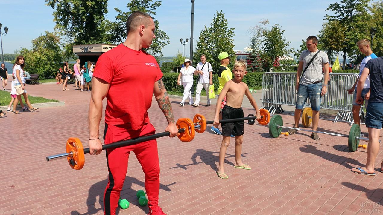 Мальчик и инструктор со штангами в День физкультурника в Самаре