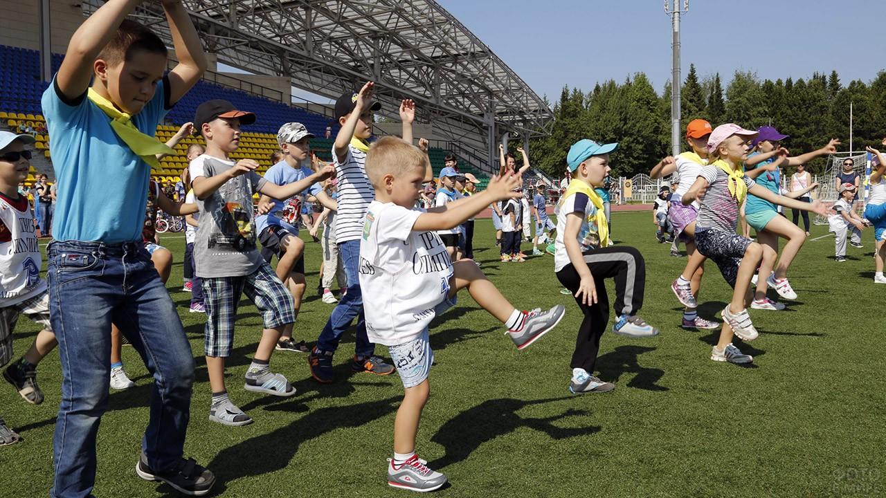 Малыши делают зарядку на стадионе в День физкультурника в Ханты-Мансийске