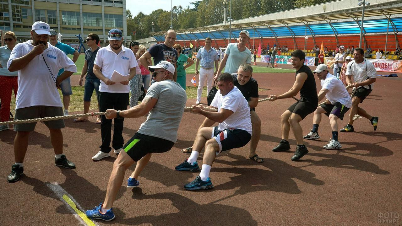 Мужская команда перетягивает канат в День физкультурника