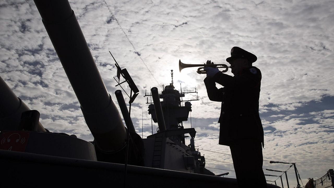 Силуэт военного с горном на фоне линкора в гавани Пёрл-Харбор