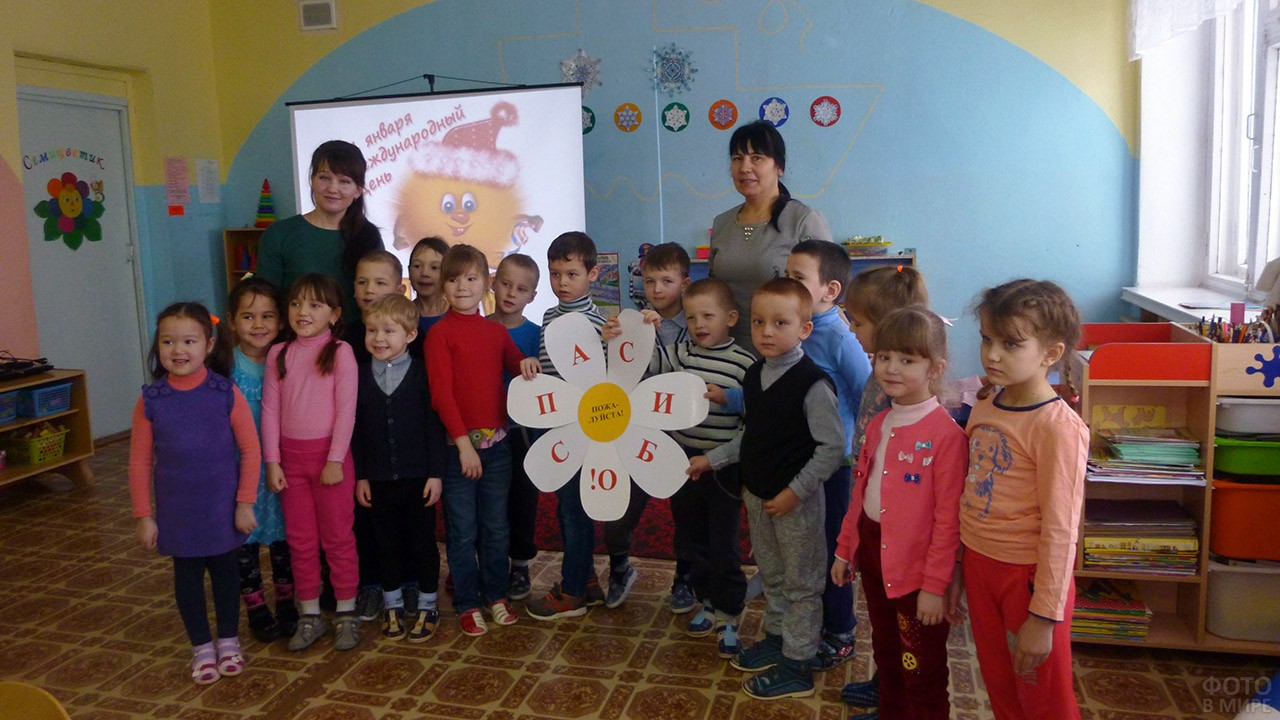Дети и воспитательницы держат плакат-ромашку со словом Спасибо