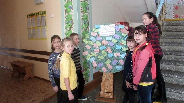 Дети у дерева-стенда с открытками к Международному дню Спасибо