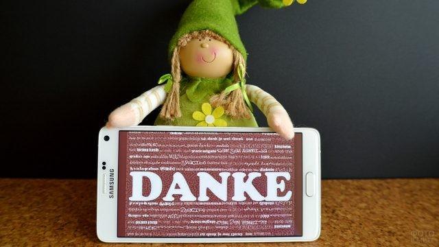 Кукла держит смартфон с надписью Спасибо на немецком